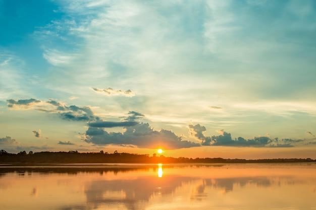 Piękny zachód słońca za chmurami powyżej tła krajobrazu jeziora.
