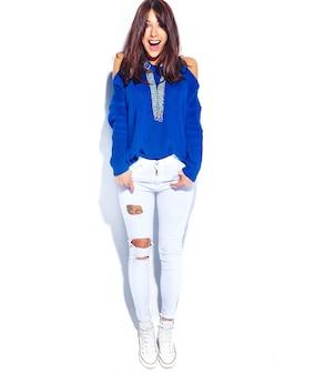 Piękny zdziwiony modniś brunetki kobiety model w przypadkowego stylowego lata błękitnym pulowerze odizolowywającym na białym tle. pełna długość