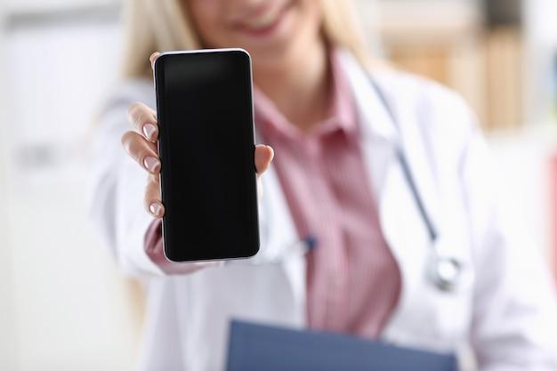 Piękny żeński blondynki lekarki mienia smartphone