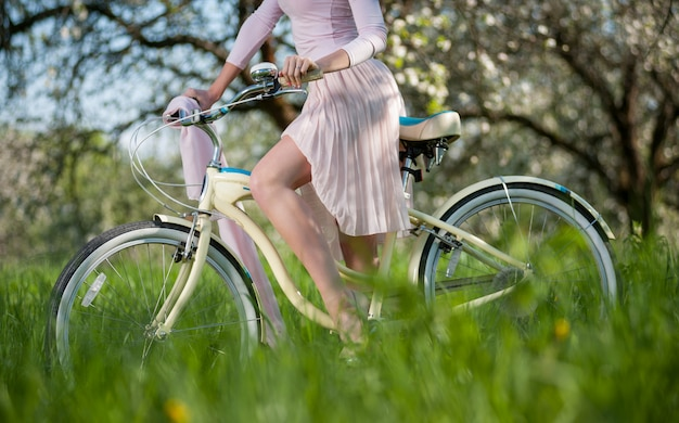 Piękny żeński cyklista z retro bicyklem w wiosna ogródzie