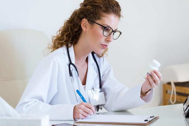 Piękny żeński farmaceuty mienia słój pigułki w rękach w biurze.