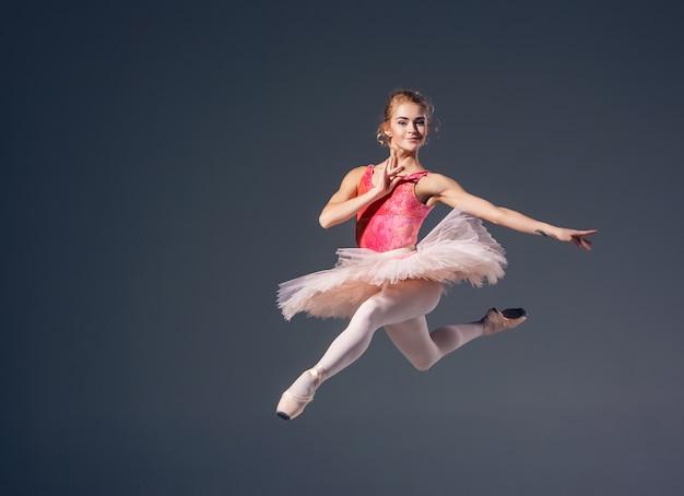 Piękny żeński tancerz na szarym tle. balerina ma na sobie różowe buty tutu i pointe.