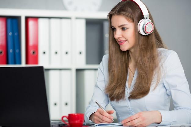 Piękny żeński uczeń słucha muzyka i uczy się z hełmofonami. trzymaj rączkę w ręce i patrz na monitor laptopa
