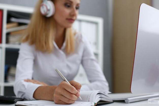 Piękny żeński uczeń z hełmofonów pisać