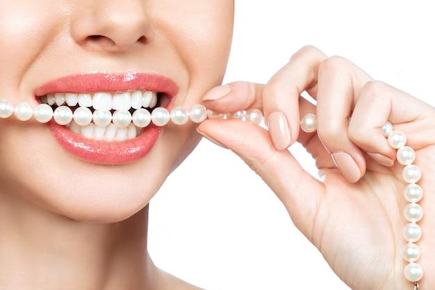 Piękny żeński uśmiech i perełkowa kolia, zdrowia dentystycznego pojęcie