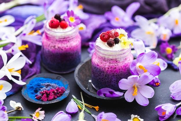 Piękny zestaw fioletowych wiosennych wegańskich koktajli ozdobionych kolorowymi kwiatami