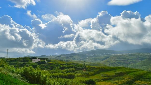Piękny zielony krajobraz z dużą ilością gór pod zachmurzonym niebem