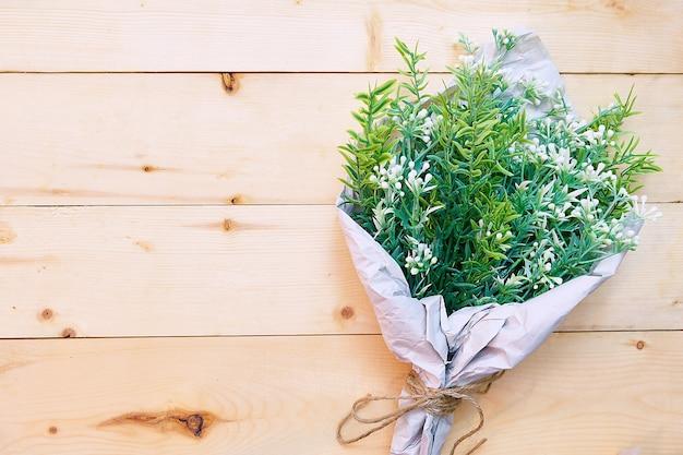 Piękny zielony kwiatu bukiet na drewnianym stołowym tle