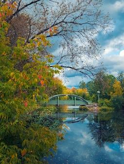 Piękny zielony most nad stawem w parku miasta tichwin w rosji wczesną jesienią