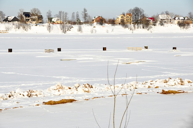 Piękny zima krajobraz - dom na wsi, rzeka i drzewa zakrywający z białym śniegiem