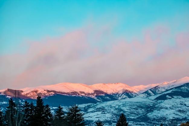 Piękny zimowy krajobraz rozświetlony promieniami słońca o poranku pokryty śniegiem dramatyczne niebo
