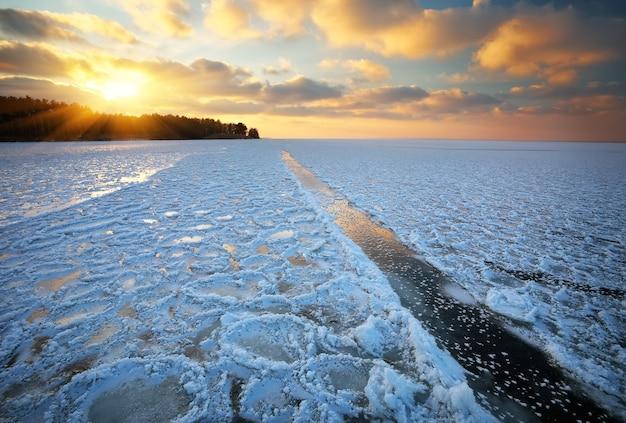Piękny zimowy krajobraz z zachodem słońca na niebie i zamarzniętym jeziorze
