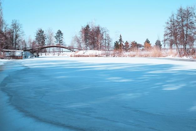Piękny zimowy krajobraz z zamarzniętą rzeką i błękitnym niebem