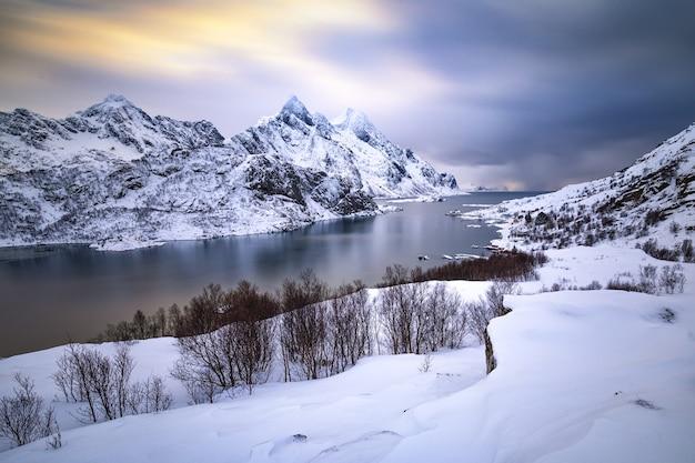 Piękny zimowy krajobraz ze śnieżnymi górami i lodowatą wodą