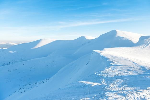 Piękny zimowy krajobraz ze śnieżnymi górami pod błękitnym niebem