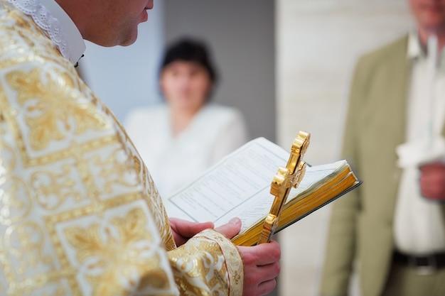 Piękny złoty krzyż w męskich rękach księdza w złotej szacie na ceremonii w chrześcijańskim kościele katedralnym, święte wydarzenie sakramentalne. kapłan trzymający biblię