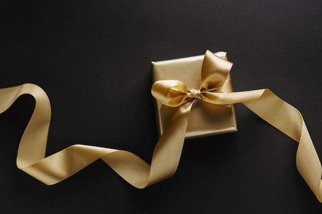 Piękny złoty prezent świąteczny ze złotą wstążką na czarnym tle