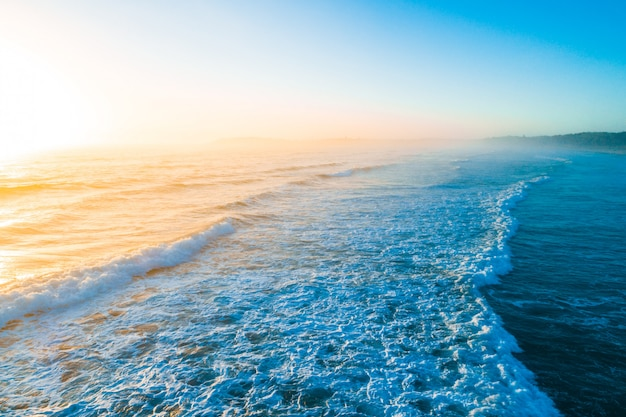 Piękny złoty wschód słońca nad błękitnymi ocean fala z kopii przestrzenią