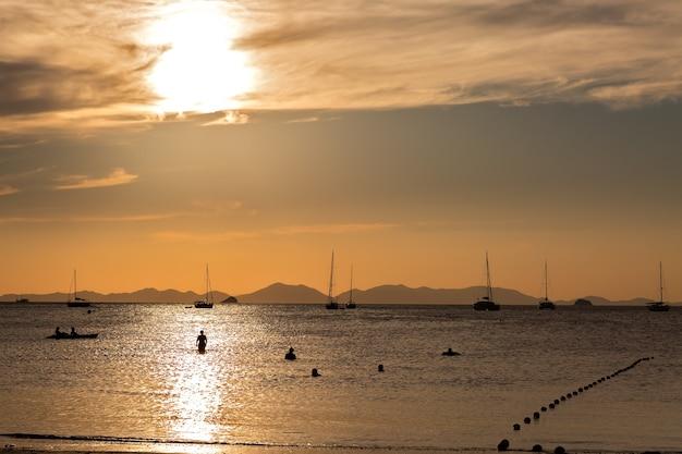 Piękny złoty zachód słońca ze ścieżką słońca i sylwetkami ludzi w wodzie podziwiających zachód słońca