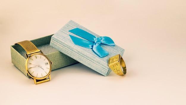 Piękny złoty zegarek i pierścionek w pudełku z niebieską wstążką