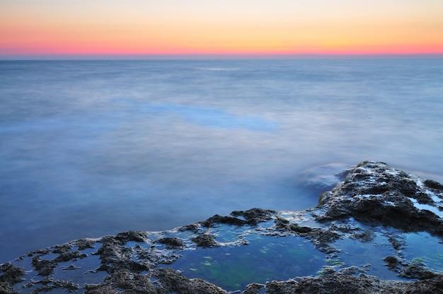 Piękny zmierzch nad falistym burzowym czarnego morza skalistą linią brzegową na krym na letnim dniu