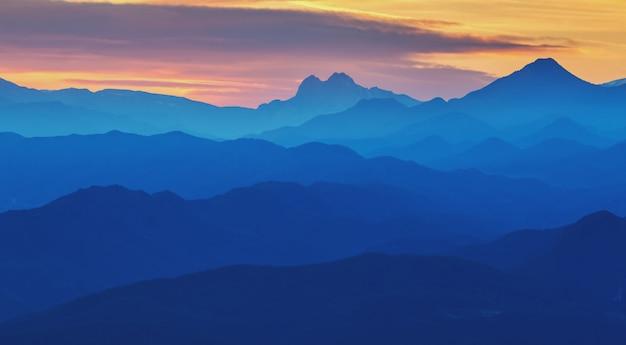 Piękny zmierzch zaświeca w hiszpańskich górach (serra d entreperes). sylwetki linii górskich.