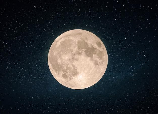 Piękny żółty księżyc w pełni z kraterami na gwiaździstym niebie.