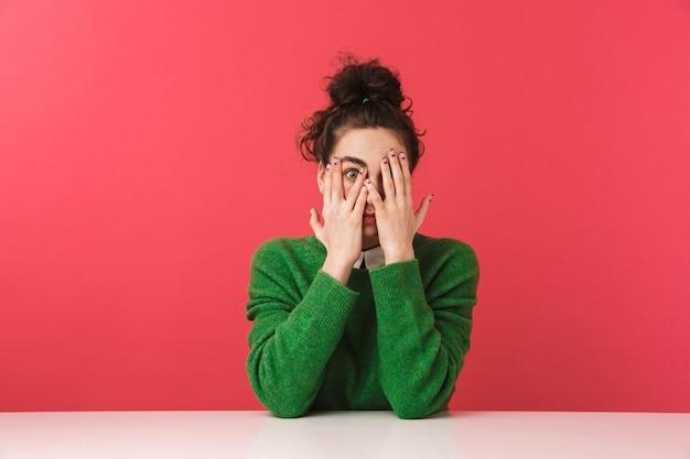 Piękny zszokowany młody student dziewczyna siedzi przy stole na białym tle, zakrywając twarz