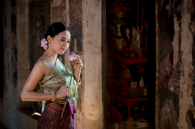 Pięknych kobiet dziewczyny mienia ręki tajlandzki lotos w tradycyjnym tajlandzkim kostiumu z świątynnym ayutthaya.
