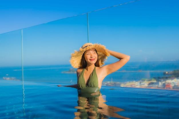 Pięknych młodych azjatykcich kobiet szczęśliwy uśmiech relaksuje wokoło plenerowego pływackiego basenu w hotelowym kurorcie dla podróży w wakacje wakacje