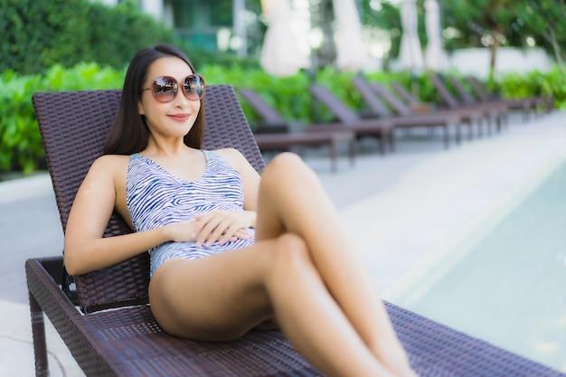 Pięknych młodych azjatykcich kobiet szczęśliwy uśmiech relaksuje wokoło plenerowego pływackiego basenu w hotelowym kurorcie