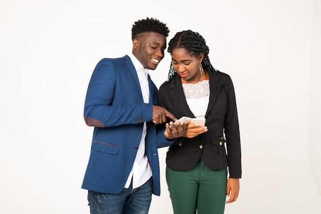 Pięknych młodych ludzi afryki na białym tle z telefonami w ręce