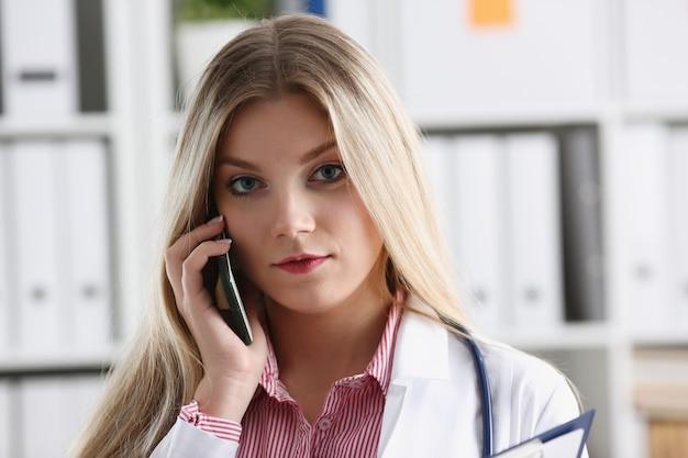 Pięknych żeńskich blondynów doktorski opowiadać na telefonie
