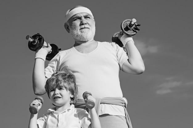 Pielęgnacja ciała i opieka zdrowotna, old vs voung. dziadek i dziecko do podnoszenia ciężarów. starszy mężczyzna i dziecko