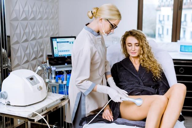 Pielęgnacja ciała i zabiegi spa. zabieg modelujący sylwetkę kawitacji ultradźwiękowej. młoda ładna blond kobieta zaczyna antycellulitową i przeciwtłuszczową terapię w salonie piękności.