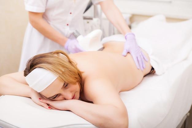 Pielęgnacja ciała. kobieta jest w trakcie zabiegu w klinice lipomassage