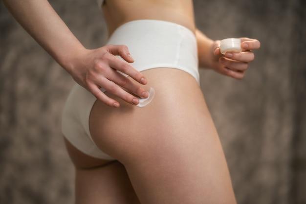Pielęgnacja ciała. kobieta nakłada krem na nogi i pośladki. kobieta stosuje krem kosmetyczny na cellulit