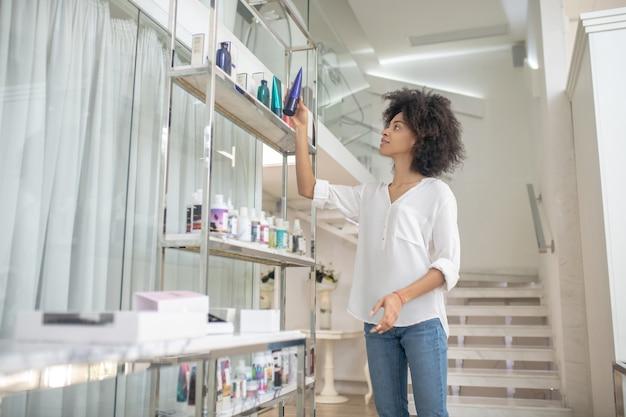 Pielęgnacja ciała. młoda kobieta z ciemnymi kręconymi włosami w białej bluzce stojącej w pobliżu stojaka z kosmetykami patrząc z zainteresowaniem