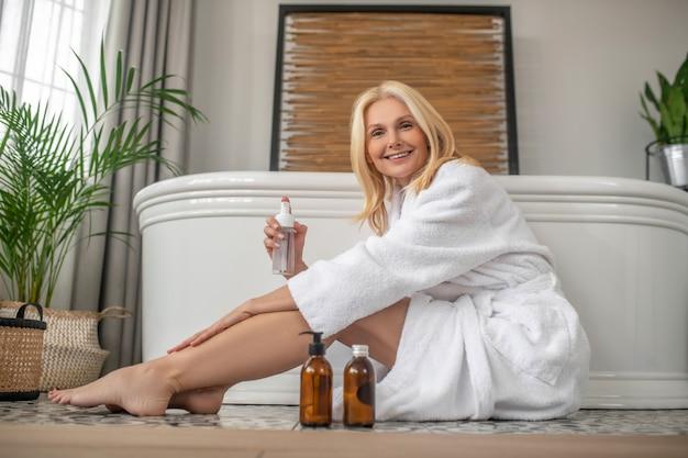 Pielęgnacja ciała. śliczna blondynka siedzi na podłodze w łazience i nakłada krem na nogi