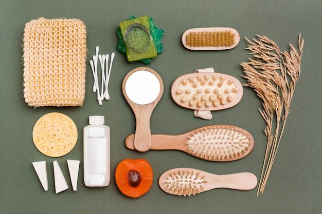 Pielęgnacja ciała. zestaw łazienkowy - mydło, myjka, masażer, szampon, lusterko, gąbki i szczotka na zielonym tle.