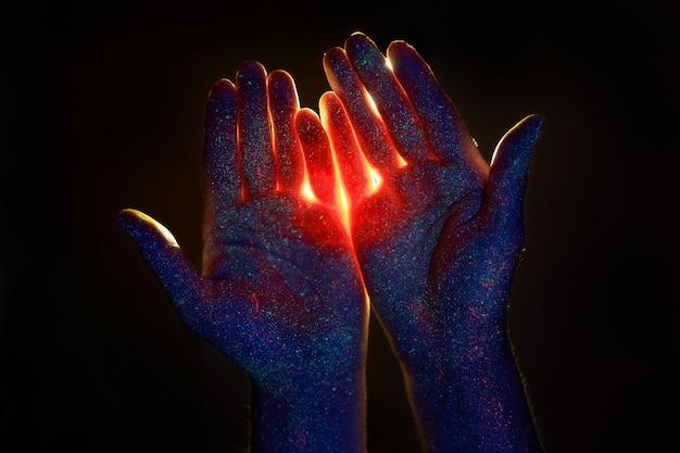 Pielęgnacja dłoni w świetle ultrafioletowym w kroplach kolorowej farby. światło przez dłonie, boga i religię. kosmetyki do rąk