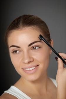 Pielęgnacja i makijaż brwi. młoda kobieta modeluje brązowe brwi