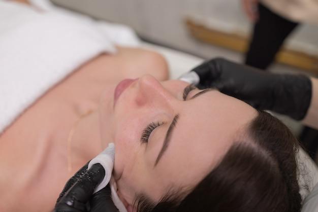 Pielęgnacja i ochrona skóry twarzy. młoda kobieta na wizytę u kosmetyczki. specjalista nakłada na twarz kremową maskę.