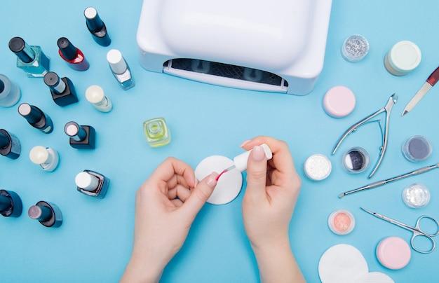 Pielęgnacja paznokci. jasnoniebieskie tło. ręce kobiet w pobliżu zestawu profesjonalnych narzędzi do manicure.