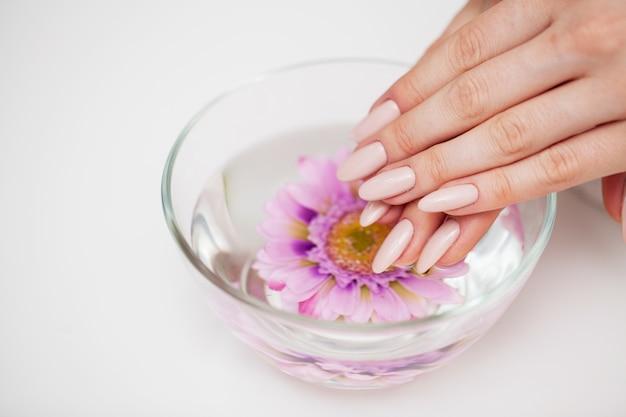 Pielęgnacja paznokci, kobieta pokazuje świeży manicure wykonany w studiu kosmetycznym