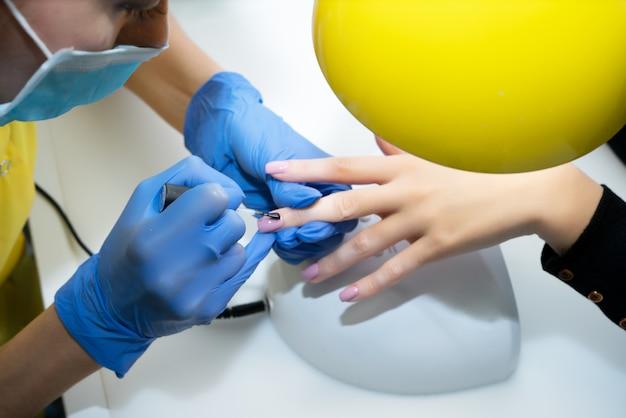 Pielęgnacja paznokci. manicure w salonie. mistrz pielęgnuje dziewczynę, piękno i zdrowie. proces manicure. mistrz w maskach i rękawiczkach. lakier do paznokci.