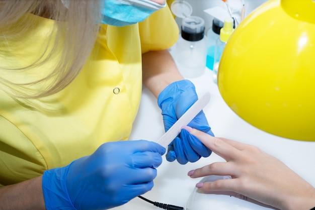 Pielęgnacja paznokci. manicure w salonie. mistrz pielęgnuje dziewczynę, piękno i zdrowie. proces manicure. mistrz w maskach i rękawiczkach.