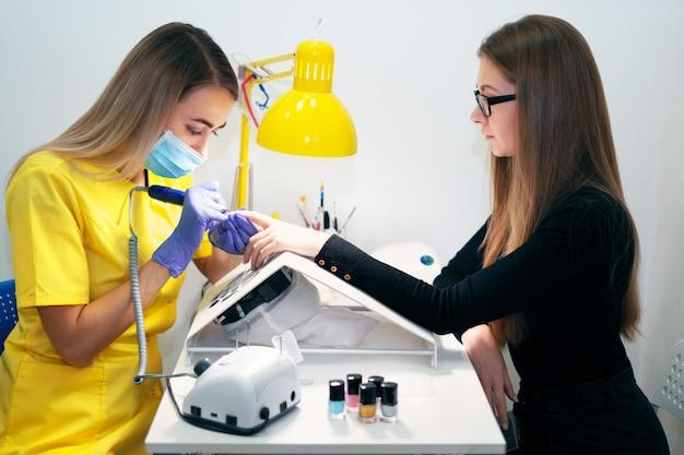 Pielęgnacja paznokci. manicure w salonie. mistrz pielęgnuje dziewczynę, piękno i zdrowie. proces manicure.