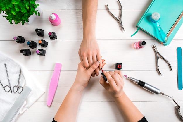 Pielęgnacja paznokci. zbliżenie kobiece dłonie zgłoszenia paznokci z profesjonalny pilnik w salonie piękności paznokci. widok z góry