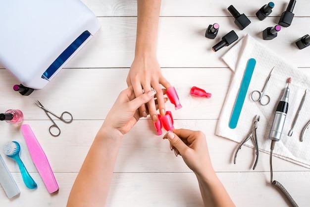 Pielęgnacja paznokci. zbliżenie kobiece dłonie zgłoszenia paznokci z profesjonalny pilnik w salonie piękności paznokci. zbliżenie: kosmetyczka robi doskonały manicure na rękach kobiety. higiena paznokci. widok z góry